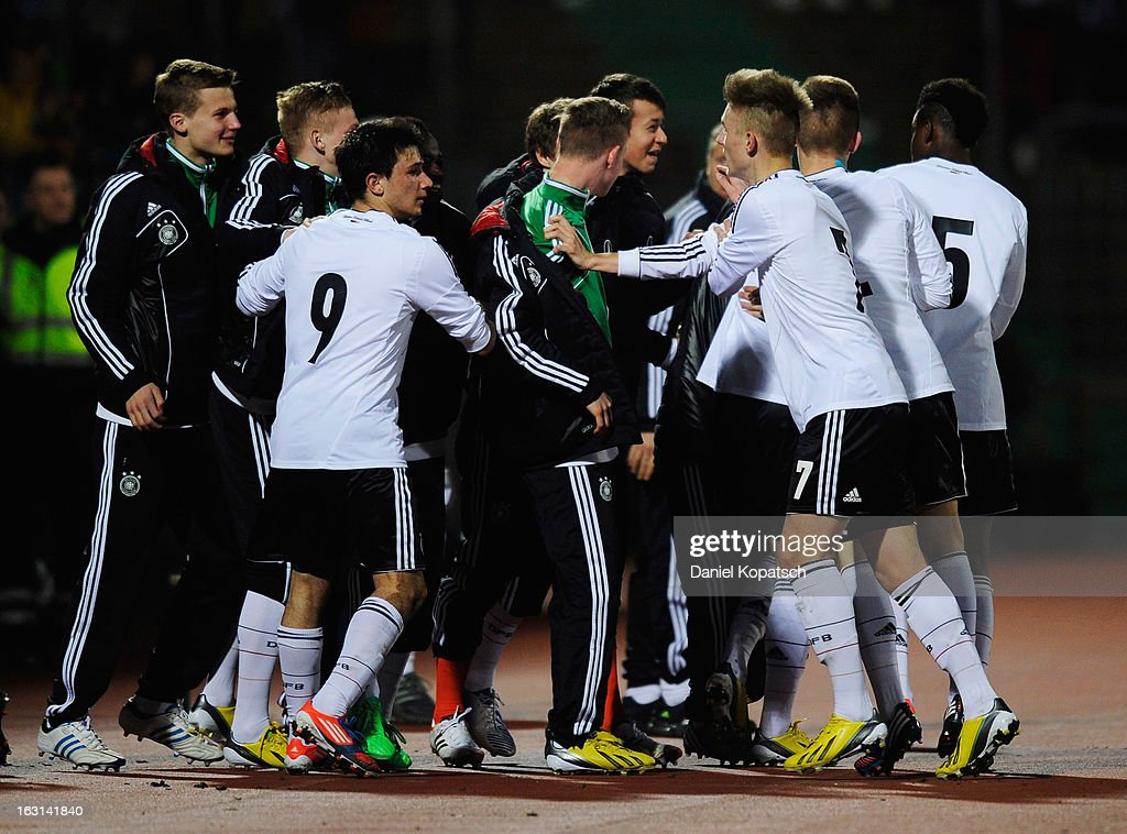 Porath Finn (obscured) is surrounded by Germany team-mates in celebration of their team's first goal during the U16 international friendly match between Germany and Italy on March 5, 2013 at Waldstadion in Homburg, Germany.