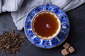Porcelain cup with a pattern full of black tea on a dark background. Hot drink - black tea