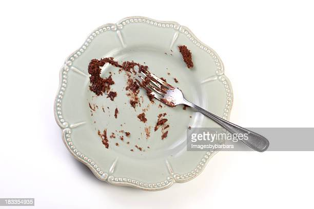 Porcelain plate with fork and pieces of chocolate cake
