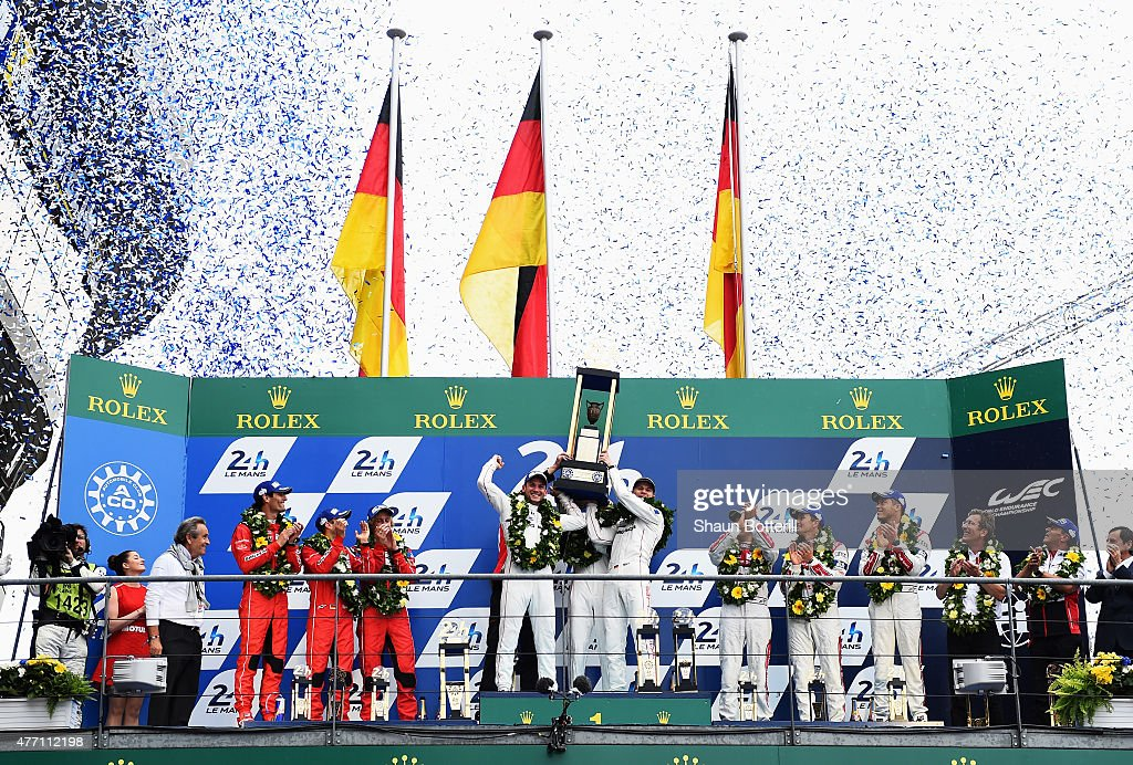 Porche Team Nico Hulkenberg Earl Bamber and Nick Tandy celebrate winning the Le Mans 24 Hour race at the Circuit de la Sarthe on June 14 2015 in Le...
