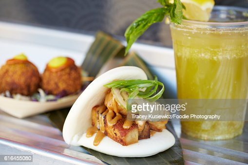 Pork belly on a Chinese steamed bun and rice ball served on a food cart : Stock Photo