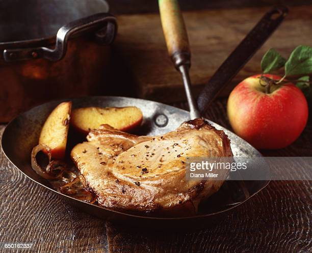 Pork chop sauteed with apple and onions in vintage frying pan