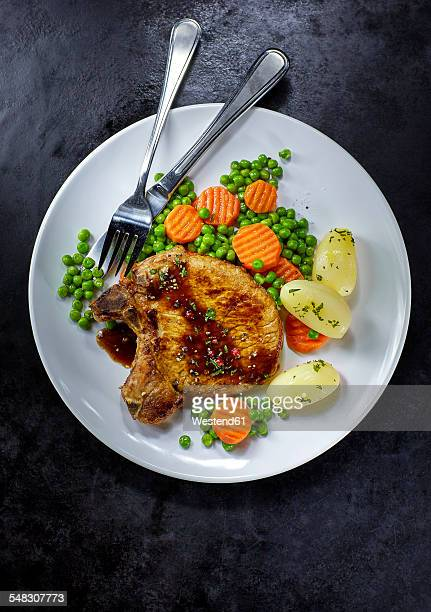 Pork chop with carrots, peas and boiled potatoes on plate