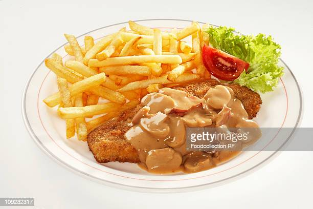 Pork escalope with chips and mushroom sauce on plate