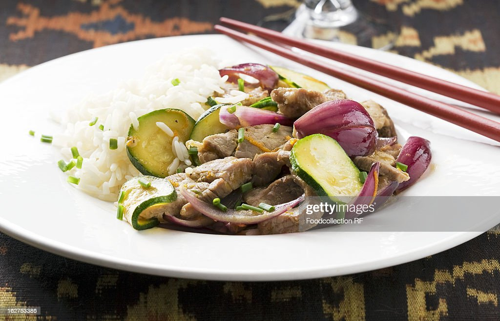 Pork fillet with courgette, onions and orange zest : Stock Photo