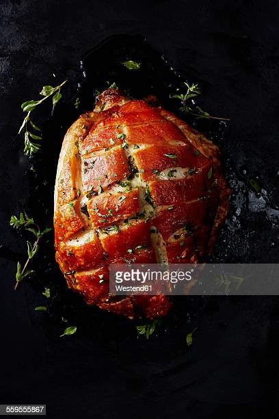 Pork roast with crackling on black background