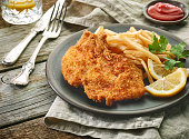 pork schnitzel and fried potatoes on wooden table