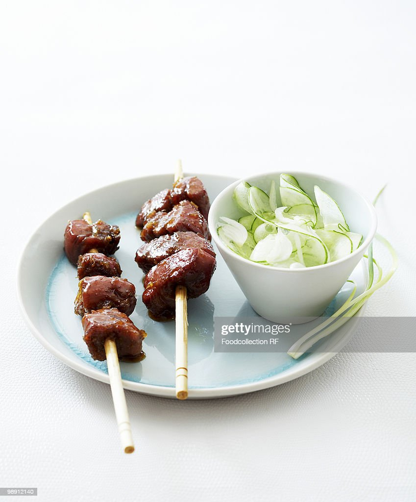 Pork skewers with cucumber salad on white background, elevated view, close-up : Stock Photo