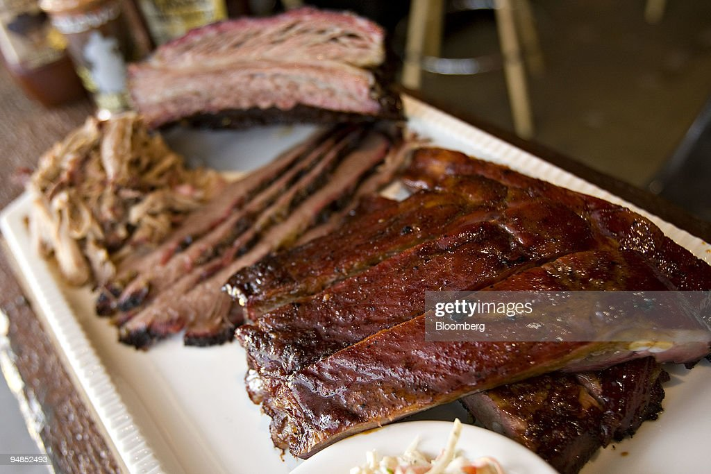 Pork Spare Ribs right are displayed for a photograph with Beef Short Rib top Pulled Pork left and strips of Beef Brisket center at Wildwood Barbeque...