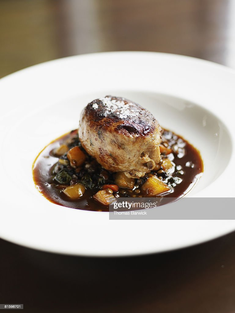 Pork with French green lentils, braised mustard greens, roasted beets, currants and pork sugo : Stock Photo