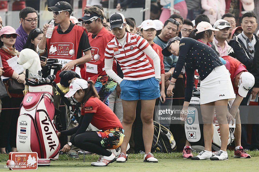 Pornanong Phatlum(left) of Thailand with Xiyun Lin of China(center) and So Yeon of South Korea(right) warm up and get ready to start during the final round of the Reignwood LPGA Classic at Pine Valley Golf Club on October 6, 2013 in Beijing, China.