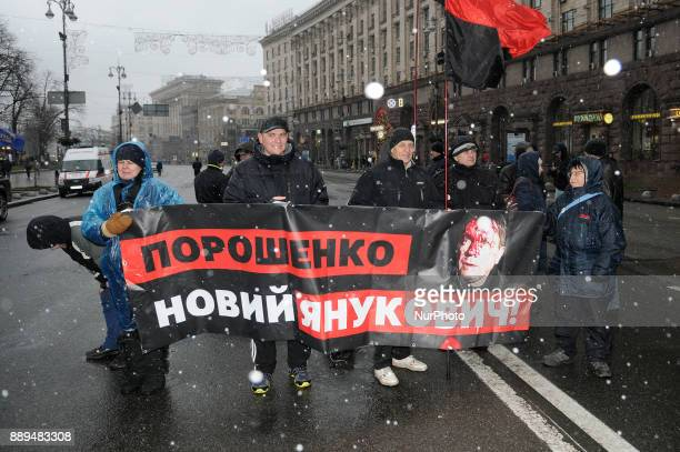 Poroshenko is the new Yanykovych is seen on a banner during a rally in Kiev Ukraine on December 10 2017 lack of progress in combating severe...