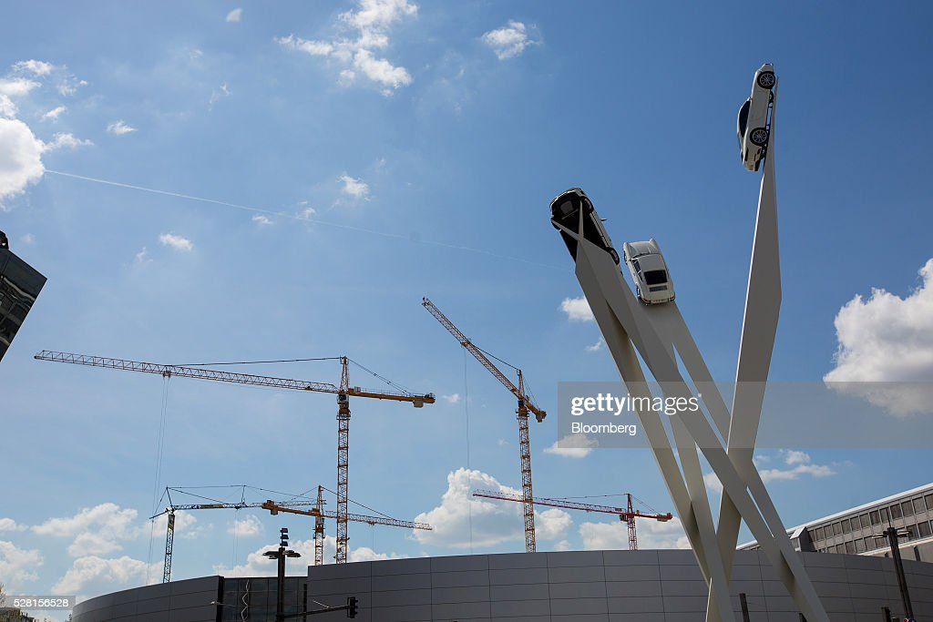 Porsche 911 luxury automobiles sit elevated on a sculpture as construction cranes stand beyond while building work continues on a new automobile bodyshop, at Porsche AG's headquarters in Stuttgart, Germany, on Wednesday, May 4, 2016. After the upscale Audi brand, Porsche is the second-largest earnings contributor at Volkswagen and generates the group's highest margins. Photographer: Krisztian Bocsi/Bloomberg via Getty Images