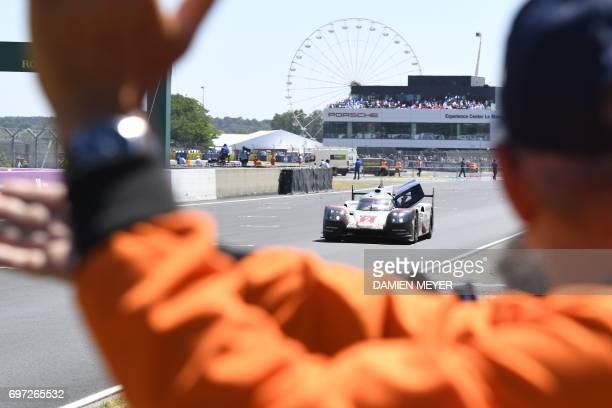 Porsche 919 Hybrid N°2 team German's driver Timo Bernhard is applauded by marshalls after winning the Le Mans 24 hours endurance race on June 18 2017...