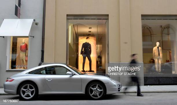 A Porsche Carrera car parks in front of the store of luxury fashion brand Jill Sander in Munich southern Germany on April 29 2013 AFP PHOTO/CHRISTOF...
