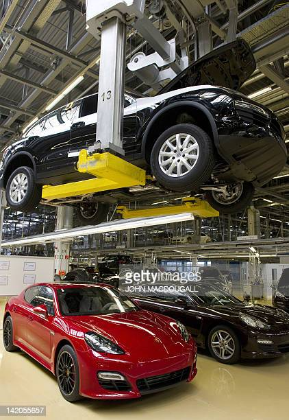 A Porsche Cayenne model is lifted past a Panamera model on the production line of the German luxury carmaker Porsche plant in Leipzig eastern Germany...