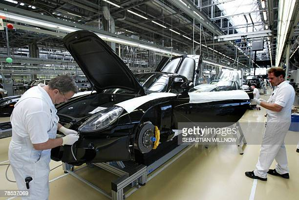 Porsche workers assemble a Porsche Carrera GT car in the eastern German plant of the German luxury carmaker 07 September 2005 Leipzig in the federal...