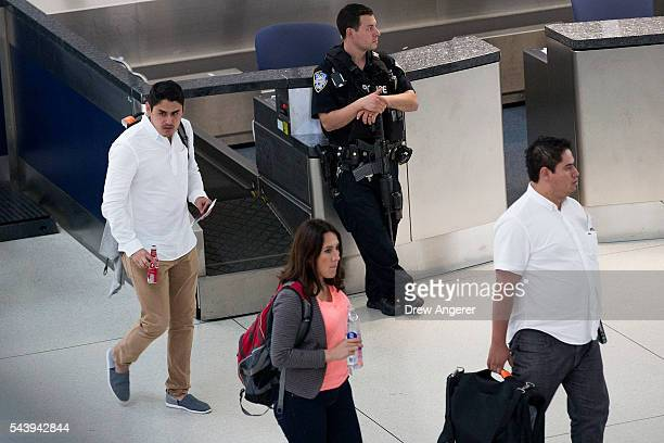Port Authority police officer holds a rifle as passengers walk through the departures terminal at John F Kennedy International Airport June 30 2016...