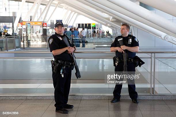 Port Authority police officers stand guard near a departures entrance at John F Kennedy International Airport June 30 2016 in the Queens borough of...