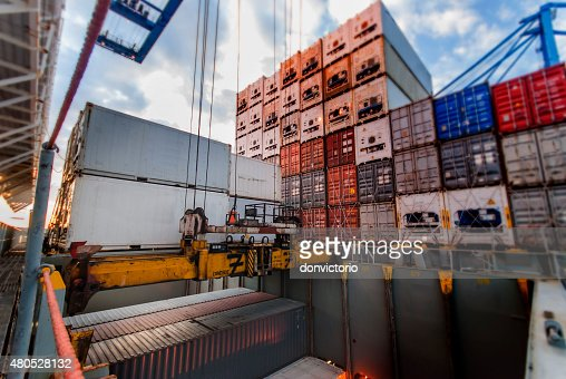 Port crane lifts container during cargo operation : Stock Photo