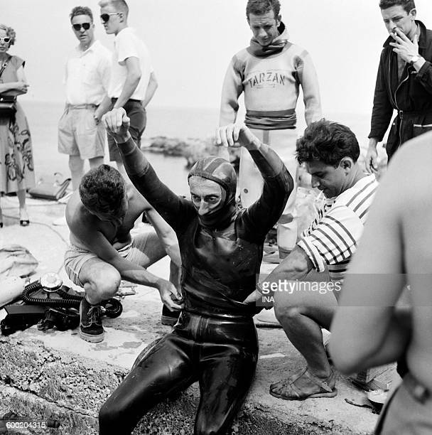 commander Jacques Yves Cousteau putting on his combination of dive helped by Hubert Falco for the program 'Live from' on the scuba diving