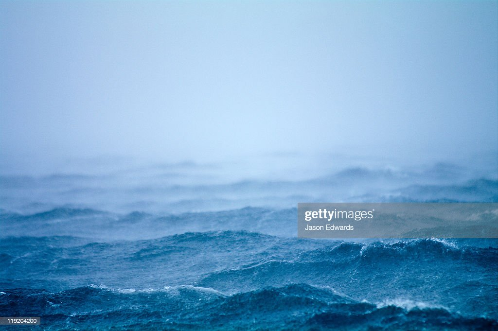 A tropical storm lashes the surface of the ocean with wind and rain.