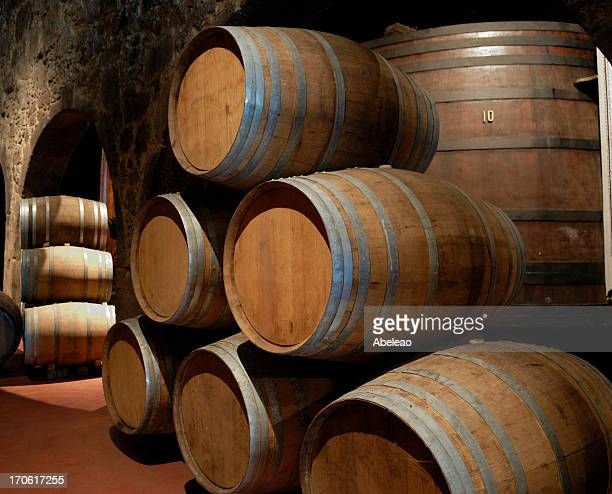 Port wine cellar with many stacked wooden barrels
