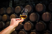 port wine in wine cellar, glass of alcohol in cellar, glass of wine in hand, wine degustation
