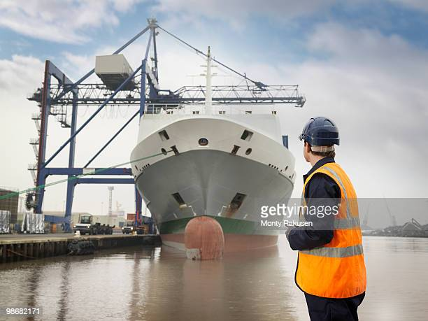 Port Worker Looking At Container Ship