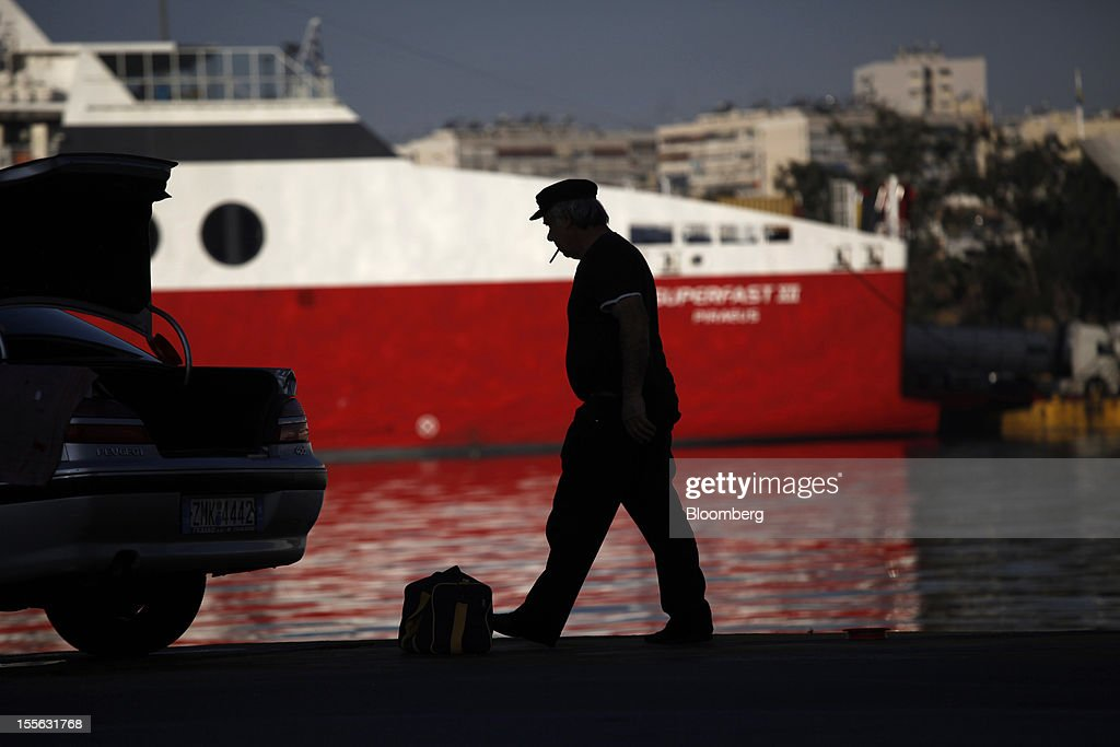 A port worker smokes a cigarette on the dockside at Piraeus port at the start of a general strike in Athens, Greece, on Tuesday, Nov. 6, 2012. Greece headed for a cliffhanger vote on austerity measures needed to keep the bailout on track as a 48-hour general strike began and European officials squabbled over the timing of a deal to unlock rescue funds. Photographer: Kostas Tsironis/Bloomberg via Getty Images
