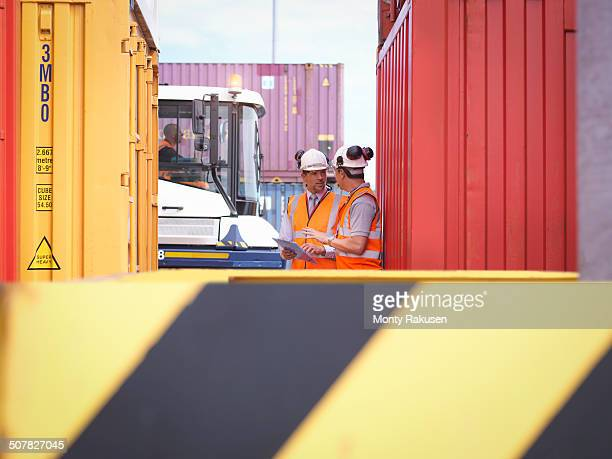 Port workers with shipping containers in port