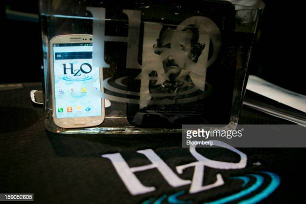 Portable electronic devices are submerged in water for a HZ0 waterproof demonstration during a press event prior to the 2013 International Consumer...