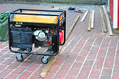 Portable Generator with wheels  on the House Construction Site. Close up on Mobile Backup Generator.
