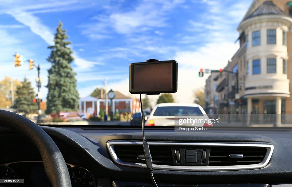 Portable GPS unit hanging on a vehicle windshield : Stock Photo