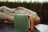 Cool green Portable small wireless speaker playing in a park