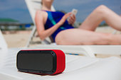 Portable speaker and female with mobile phone. Woman manage wireless bluetooth acoustic at beach