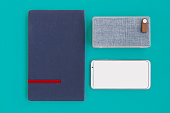 Portable wireless speaker with a generic modern smartphone or cellphone and a notebook on a solid desaturated cyan color background
