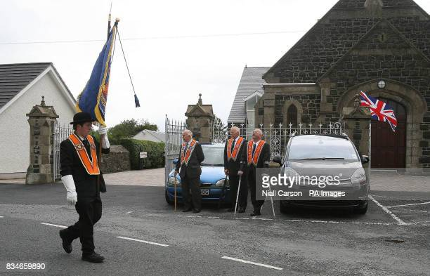 Portadown Orange men march past Drumcree church as the lodge is prevented from marching down the nationalist Garvaghy road