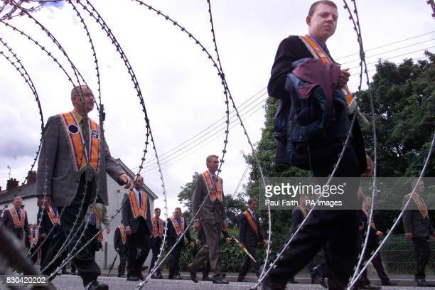 Portadown Orangemen walk past yards of barbed wire erected by the security forces near St Johns Catholic Chapel in Portadown The Orangemen were...