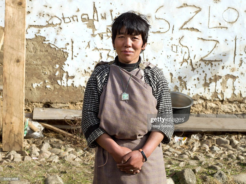 Portait of a Bhutanese woman wearing a kira the traditional dress outside her home in Yangthang village Haa valley Western Bhutan The kira is the...