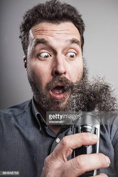 Portait of a mature man emoving his full beard