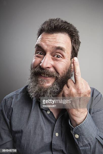 Portait of a mature man with full beard, showing middle finger