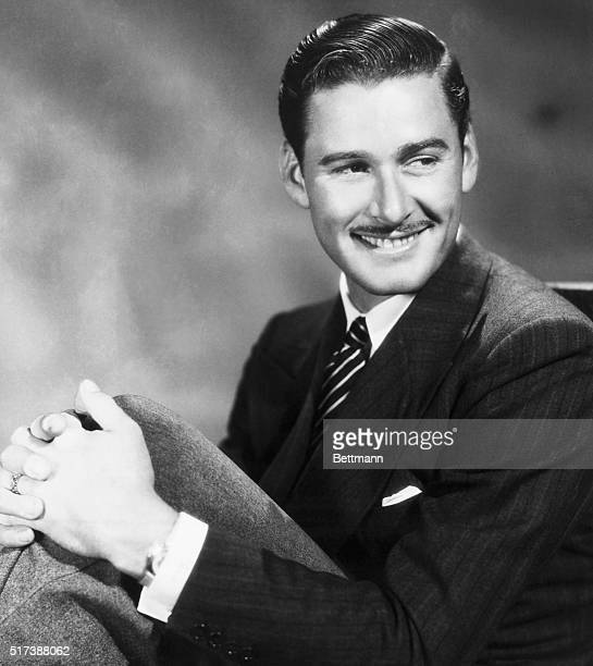 Portait of actor Errol Flynn with his hands around his knees Undated photograph
