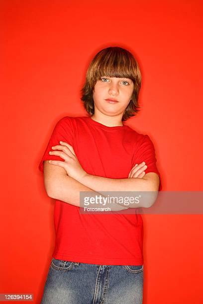 Portait of Caucasian boy with arms crossed standing against red background.