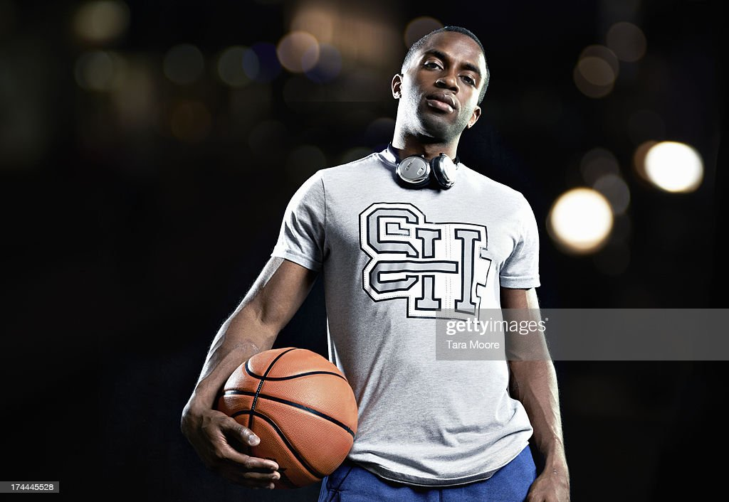 portait of man holding basketball with headphones : Stock Photo