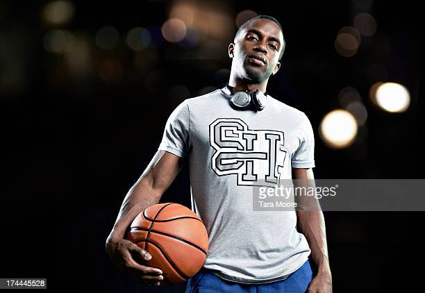 portait of man holding basketball with headphones