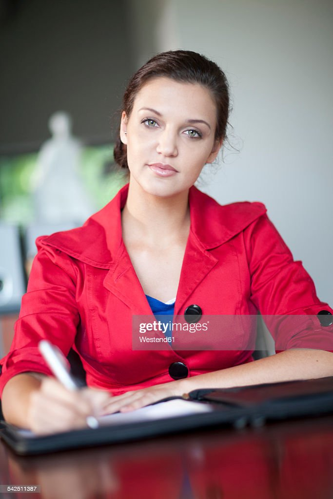Portait of serious looking woman with red jacket in an office