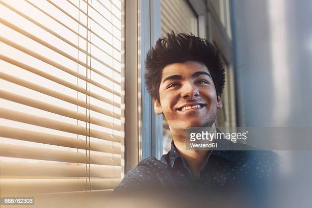 Portait of young man on window, smiling, middle eastern ethnicity