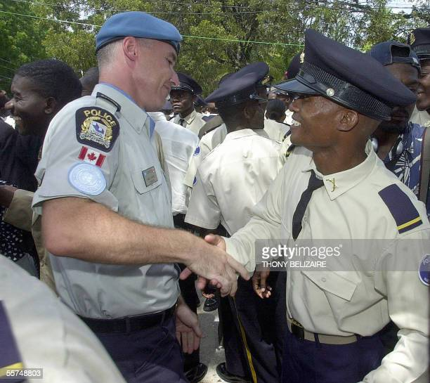 UN Police officer Alain Landry from Canada congratulates a Haitian police officer upon his graduation 23 September 2005 in PortauPrince The new class...