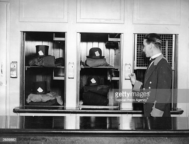 A porter at London's Savoy Hotel demonstrating an electric lift for hats coats and umbrellas
